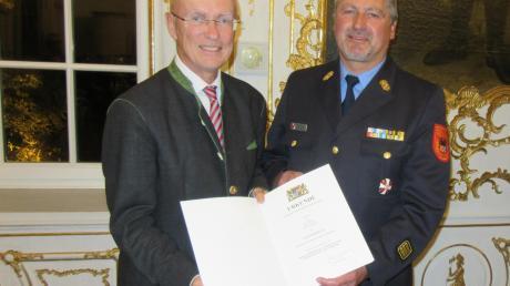 Schwabens Regierungspräsident Karl Michael Scheufele (links) überreichte das Steckkreuz und die Urkunde an Jürgen Scheerer.