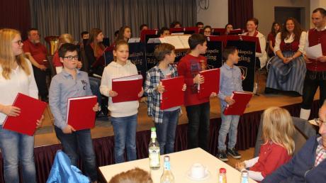 Neue Mitglieder wurden in die Jugendkapelle aufgenommen. Als symbolische Geste bekamen sie die P-Ordner für die Noten überreicht.
