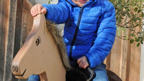 Der kleine Tim auf dem gespendeten Holzpferd.