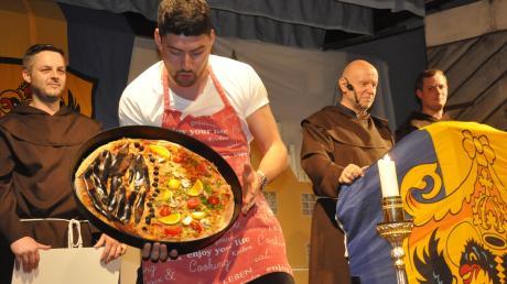 """Eine Pizza mit """"46 Prozent schwarzer Belag"""" lieferte Bote Sebastian Heckl beim """"Donauwörther Nockherberg"""" in Auchsesheim für den Landtagsabgeordneten Wolfgang Fackler. Am Rednerpult: Fastenprediger Johann Engelschall."""