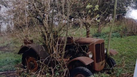 Schrottreif und von der Natur überwuchert stand der Schlepper nach dem Krieg im Garten eines Landwirts.