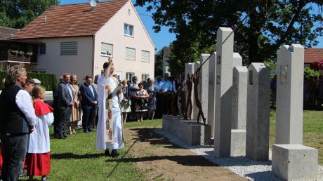 """""""An einem Strang ziehen"""" heißt es auf dem Denkmal, für das in Tagmersheim Pfarrer Tobias Scholz Gottes Segen erbat. Die Bürger des Orts feierten zusammen mit Gästen den Abschluss der Dorferneuerung."""