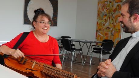 Die Bildhauerin Nathalie Schnider-Lang beherrscht auch die Nyckelharpa, ein schwedisches Musikinstrument. Rechts: Pfarrvikar Rainer Herteis.