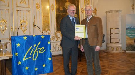 Stefan Kolonko ist seit mehr als 20 Jahren als Förster beim Zweckverband Wasserversorgung Fränkischer Wirtschaftsraum für die Waldgebiete im Wasserschutzgebiet Genderkingen im Lech-Donau-Winkel tätig. Regierungspräsident Erwin Lohner (links) hat ihn dafür ausgezeichnet.