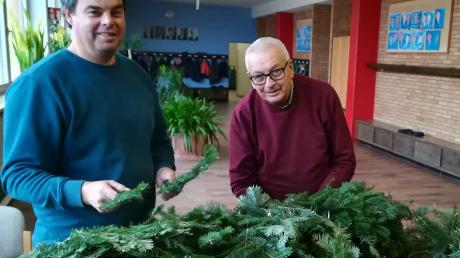 Einträchtig und mit Freude dabei: Vater und Sohn beim Flechten des aktuellen Adventskranzes.