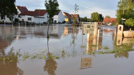 """""""Land unter"""" in Daiting: In der Ortsmitte umspülten die schmutzigen Fluten auch den Dorfbrunnen."""