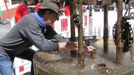Ein letzter Schlag mit dem Hammer: Bildhauer Fred Jansen bei der Arbeit am Wasserspiel des Brunnens am Marktplatz in Harburg. Jansen reparierte und rekonstruierte das durch einen Unfall beschädigte Werk.