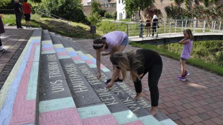 """""""Uns trennen keine Hautfarben, keine Religionen, wir sind alle Menschen"""", malen Franziska Schißler und Bernadette Rödl mit Kreide auf eine Treppe. Diese Woche haben wir sie bei einer ihrer Kreide-Aktionen in der Stadt begleitet."""