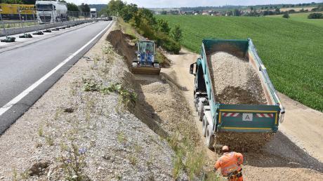 Nachdem der Hang an der B2 auf einer Länge von über 50 Metern abgerissen ist, läuft eine Notsicherung. Lastwagen schaffen Kies und große Steine heran.
