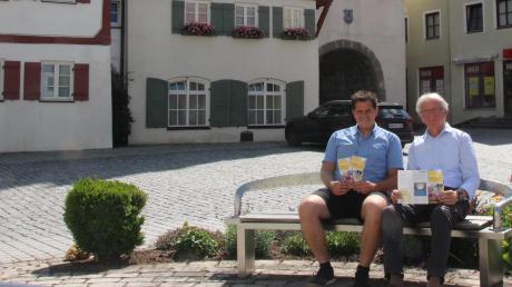 Monheims Stadtaktivmanager Peter Ferber und Heimatkundler Hanns Wenninger präsentieren vor der historischen Kulisse die neue Broschüre, die auf das Alleinstellungsmerkmal Monheims als bayerische Drei-Stämme-Stadt eingeht.
