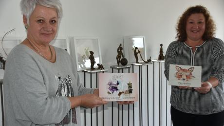 """Ines Mösle (links) und Doris Stippler präsentieren die beiden Bücher """"Weiber'gschichten – Männerkram"""" und """"Viechereien"""" mit Zeichnungen und gereimten Vierzeilern. Im Hintergrund sind einige der Bronzefiguren zu sehen, die als Grundlage für die Abbildungen dienten."""