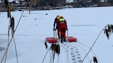 Zwei Wasserwachtler aus Donauwörth holen mit einem schwimmfähigen Eisschlitten das Hab und Gut der Eisangler ans Ufer.