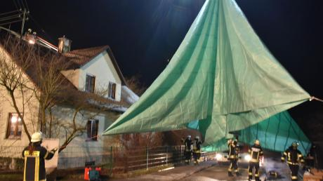 Ungewöhnlicher Einsatz: Die Feuerwehr legte in Auchsesheim eine große Plane über das Wohnhaus, das durch einen Brand schwer beschädigt wurde.