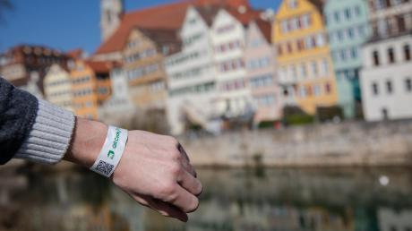 Ein Mann trägt in Tübingen ein Tagesticket-Armband. Damit kann man etwa in Geschäften einkaufen.