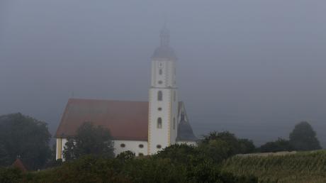 Vorgeschmack auf den Herbst: Erst Mitte des Vormittags gab am 31. August der erste Nebel nach dem meteorologischen Sommerende den Blick auf den Turm der Wallfahrtsbasilika Maria Brünnlein bei Wemding frei.