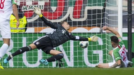 Im Hinspiel traf Marco Richter (rechts) schon in der ersten Minute für den FC Augsburg. Bayern-Torwart Manuel Neuer streckt sich vergeblich.