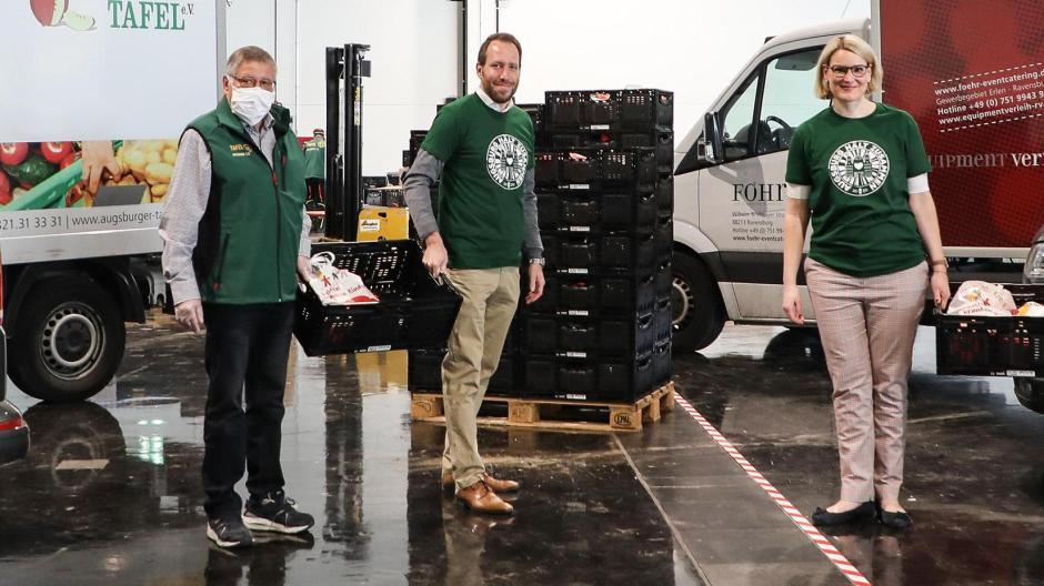 Fritz Schmidt (1. Vorstand Augsburger Tafel e.V.), FCA-Geschäftsführer Michael Ströll, und Bürgermeisterin Eva Weber (von links) halfen in einer Halle der Messe mit, die Lebensmittel zu verteilen.