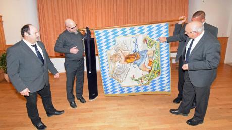 Vorstand Stefan Wild (links) und Fahnenträger Josef Axtner (rechts) bei der Präsentation der Vereinsfahne in der Jahreshauptversammlung.