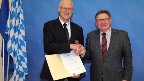 Der Meringer Helmut Röhm (links) erhielt aus den Händen des bayerischen Innenstaatssekretärs Gerhard Eck das Bundesverdienstkreuz am Bande.
