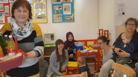 Ute Scharnagl vom Spezialitätengeschäft Hettenkofer überreichte Brigitte Dunkenberger eine Spende für die Gruppen im Mehrgenerationenhaus. Auch die kleinen Besucher der Krümelgruppe (Hintergrund) gehören zu den Nutznießern.