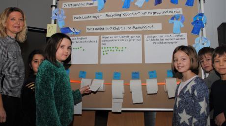 Eine Recycling-Papier-Ausstellung will an der Grundschule Kissing noch bis zum 7. Februar dieses Jahres über die Rodungen im Regenwald und deren Auswirkungen informieren. Annika Lauter, die Rektorin der Kissinger Grundschule, und Schüler der Umwelt-AG freuen sich über reges Interesse.