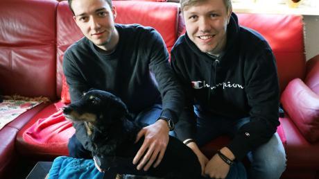 Mit Pawsthesis möchten sie gehandicapten Hunden helfen: Dominik Dogen (links) und Simon Schuß haben die von ihnen entwickelte Beinprothese an den Rumpf von Dackel Bruno angelegt. Für den perfekten Sitz fehlt noch das passende Hundegeschirr.