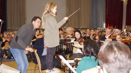 Die Augsburger Philharmoniker waren in der Luitpoldschule Mering zu Gast. Dirigent Domenkos Hejá (links) überließ bei der Carmen-Ouvertüre zwei mutigen Schülerinnen sogar kurz seinen Taktstock.