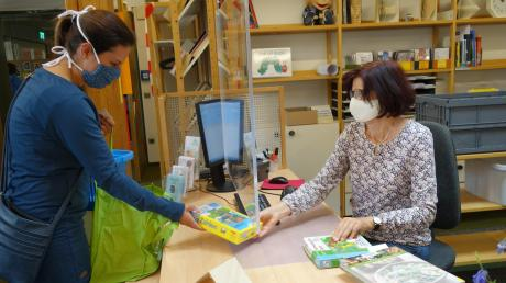 Eine Plexiglasscheibe trennt Büchereimitarbeiterin Jutta Wienken (rechts) von den Bibliotheksnutzern.