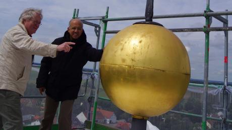 Ganz oben, zeigt sich, dass auch das goldene Kreuz repariert werden muss. Pfarrer Xavier (rechts) und Architekt Anton Kriesch.