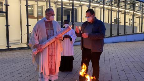 Pater Michael Pfenning entzündet die aus eingesandten Wachsresten gefertigte Osterkerze der Pallottiner  in Friedberg am Osterfeuer.