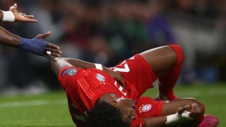 David Alaba liegt nach einem Zusammenprall im Spiel gegen Tottenham am Boden und hält sich die Rippen. Foto: Steven Paston/PA Wire/dpa
