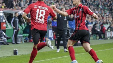 Freiburgs Torschütze Nils Petersen (l) jubelt mit Teamkollege Roland Sallai über den Treffer zum zwischenzeitlichen 1:1. Foto: Axel Heimken/dpa
