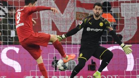 Robert Lewandowski (M) machte mit seinem Tor zum 3:0 alles klar beim Bayern-Sieg gegen den BVB. Foto: Sven Hoppe/dpa