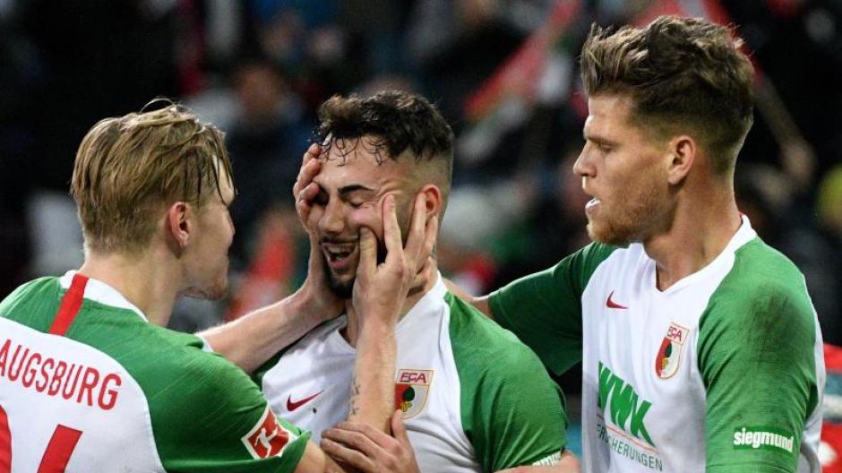 Augsburgs Fredrik Jensen (l) und Florian Niederlechner (r) freuen sich mit Torschütze Marco Richter über den Führungstreffer.