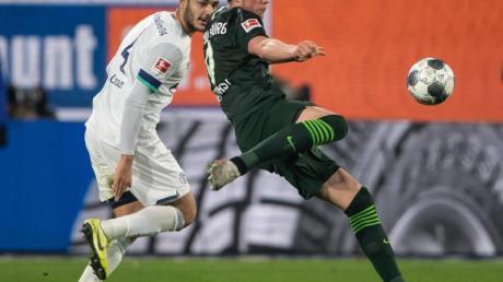 Wolfsburgs Wout Weghorst (r) zieht ab, Schalkes Ozan Kabak hat das Nachsehen.