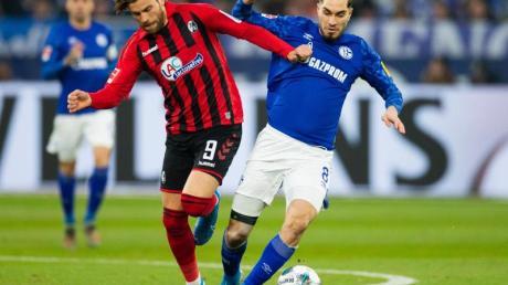Schalkes Suat Serdar (r) und Freiburgs Lucas Höler wollen an den Ball kommen.