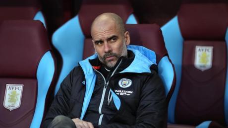 Pep Guardiola, Trainer von Manchester City, sitzt während eines Spiels auf der Trainerbank.