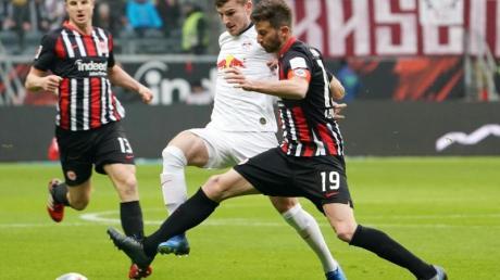 Leipzigs Timo Werner (M) kämpft mit Frankfurts David Abraham (r) um den Ball.