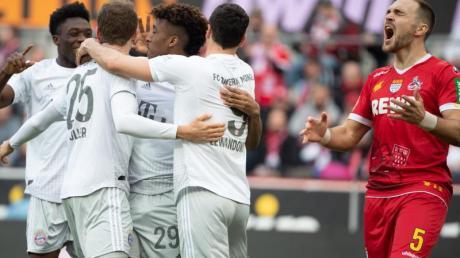Bayerns Alaba (l-r), Müller, Coman und Lewandowski feiern das 2:0. Kölns Czichos (r) schreit und ärgert sich.