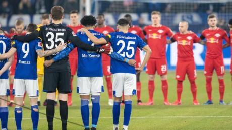 Die Teams von Schalkes und Leipzig nehmen an einer Gedenkminute teil.