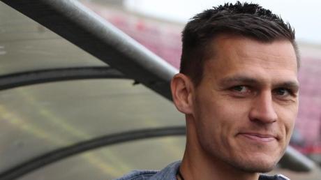 Der Trainer der Fuballerinnen des FCBayern, Thomas Wörle, lächelt vor dem Spiel in die Kamera.