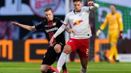 Leverkusens Sven Bender (l) geht gegen Leipzigs Patrik Schick von hinten in den Zweikampf.