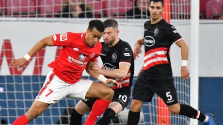 Der Mainzer Robin Quaison (l) versucht sich gegen die Düsseldorfer Valon Berisha und Kaan Ayhan durchzusetzen.