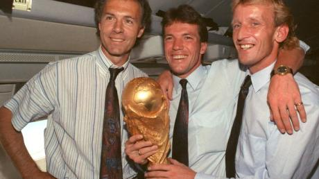 Auf dem Rückflug von Rom präsentieren DFB-Teamchef Franz Beckenbauer (l), Kapitän Lothar Matthäus (M) und Andreas Brehme den WM-Pokal.