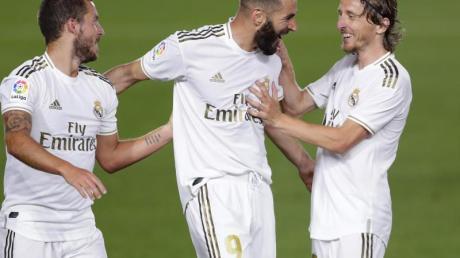 Karim Benzema (M) von Real Madrid jubelt mit seinen Mannschaftskollegen Eden Hazard (l) und Luka Modric über seinen Treffer zum 1:0.