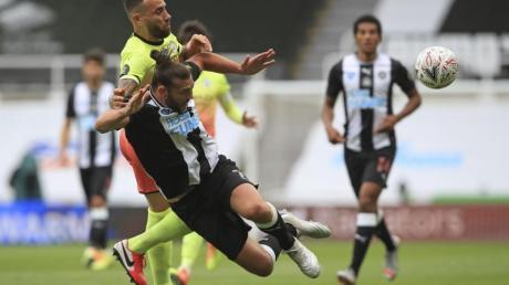 Andy Carroll (vorn) von Newcastle United wird durch Nicolas Otamendi von Manchester City gefoult.