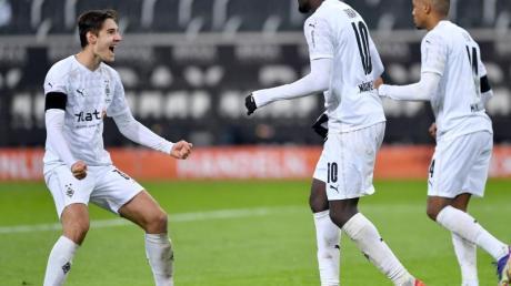 Gladbachs Florian Neuhaus (l) feiert den Treffer von Marcus Thuram (M) zum 3:1.