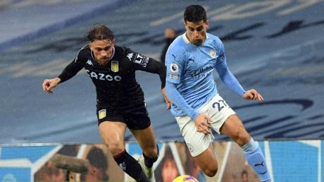 Joao Cancelo (r) von Manchester City und Aston Villas Matty Cash kämpfen um den Ball.