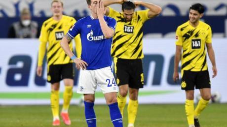 Schalkes Bastian Oczipka (vorne) steht enttäuscht im Vordergrund - im Hintergrund feiern die Dortmunder das zweite Tor ihrer Mannschaft.