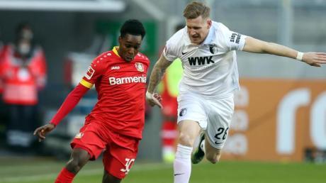 Leverkusens Jeremie Frimpong (l) und Augsburgs Andre Hahn im Zweikampf um den Ball.